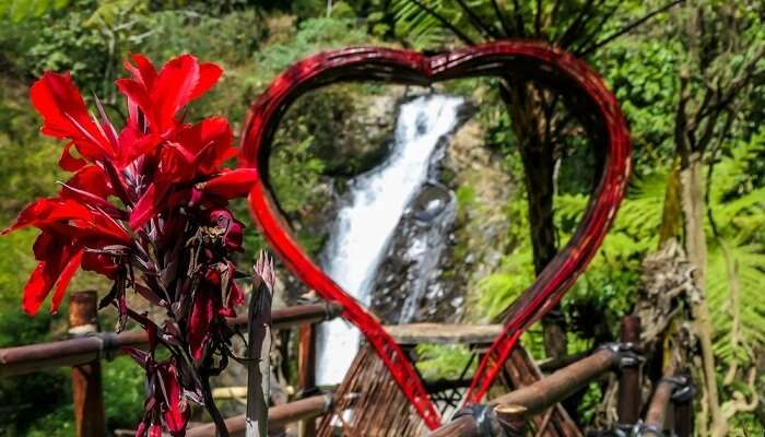 A red heart-shaped frame with Gitgit waterfall