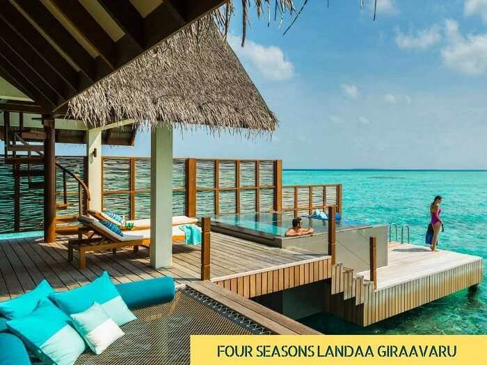 A couple enjoying in an overwater villa of the Four Seasons Landaa Giravaaru in Maldives