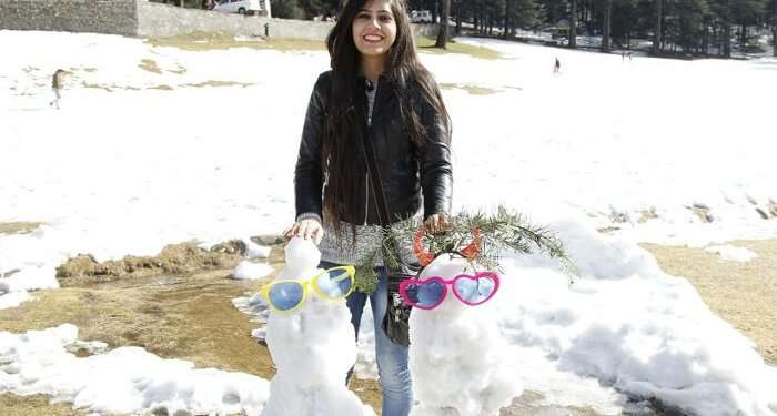 girl builds snow men in Dalhousie