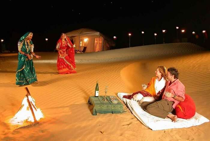 Foreign tourists enjoying a folk dance performance while glamping in Rajasthan