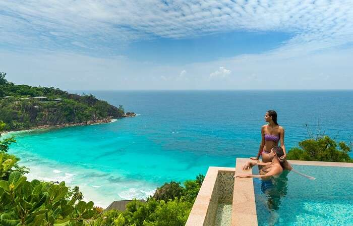 A lovey honeymooning couple gazing off at the beauty of Seychelles