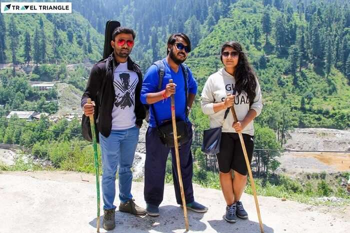 A group of travelers trekking in Kasol with walking sticks and a guitar