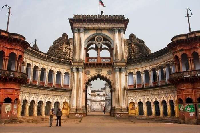 People stopped past historic indian gates with arches in ancient city of Ayodhya