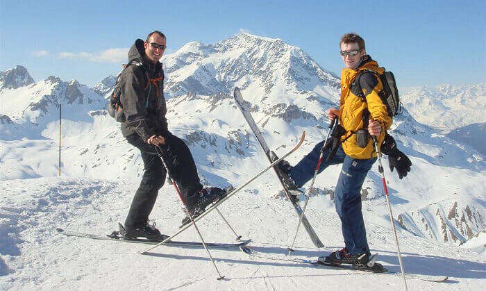 Skiers pose at the top of a slope at Tignes ski resort