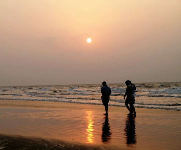 Friends enjoying a leisure walk along the beach during sunset