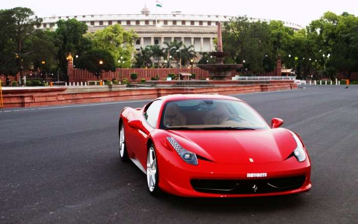 A red Ferrari on the wide roads of Delhi