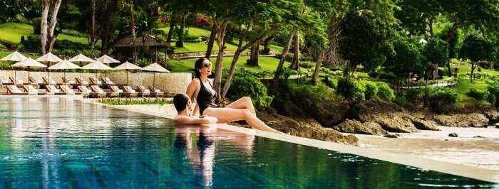 A couple enjoying in the infinity pool of one of the best hotels in Bali- Four Seasons Resort