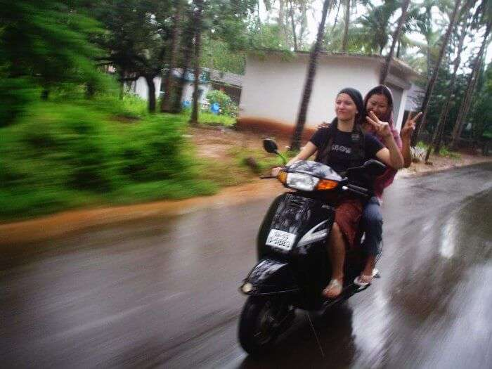 Girls enjoying a scooty ride in Goa in Monsoon