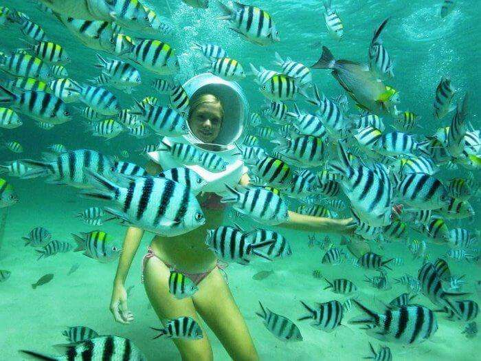 a girl enjoying undersea walk in andaman among sea fishes