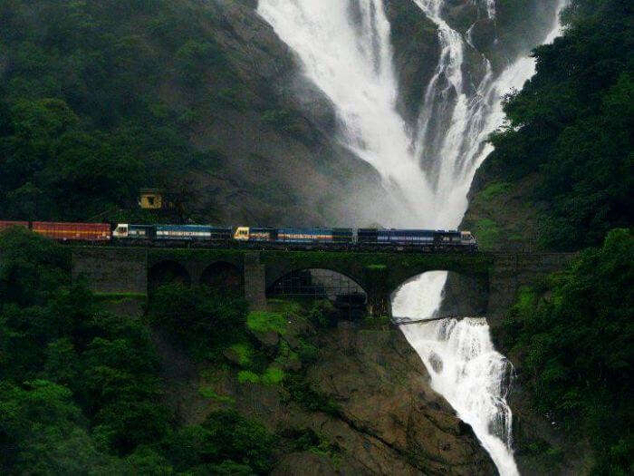 A train passes by on the railway track with the majestic Dudhsagar falls in the background