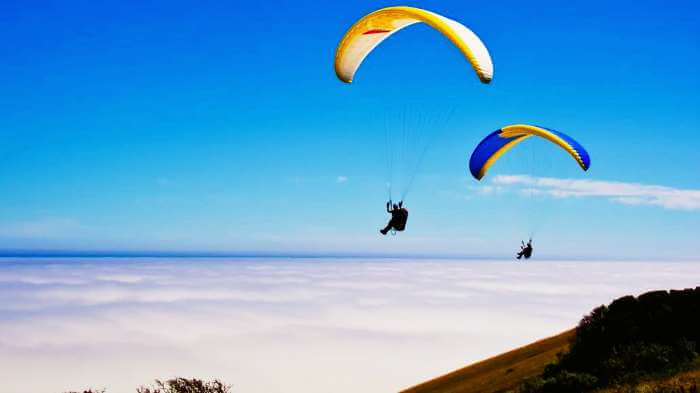 Tourists paragliding at one of the most serene offbeat weekend getaways near Mumbai - Kamshet