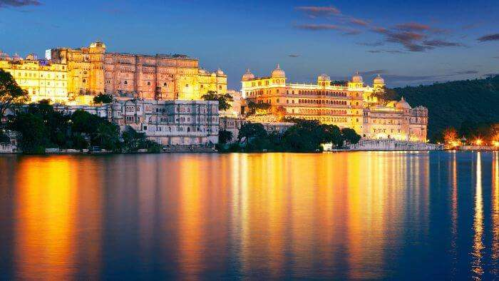 The reflection in the Pichola Lake of the well-lit Udaipur at night