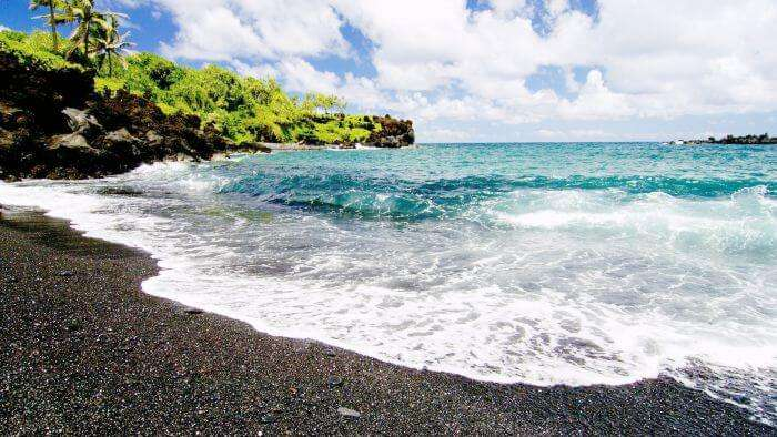Noon view of the Black Sand Beach at Punalu'u Park in Hawaii