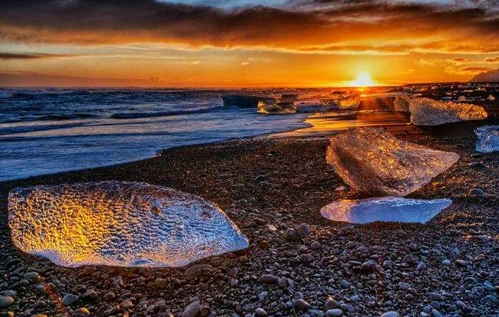 Golden sunset rays shimmering on the snow at Jokulsarlon beach in Iceland