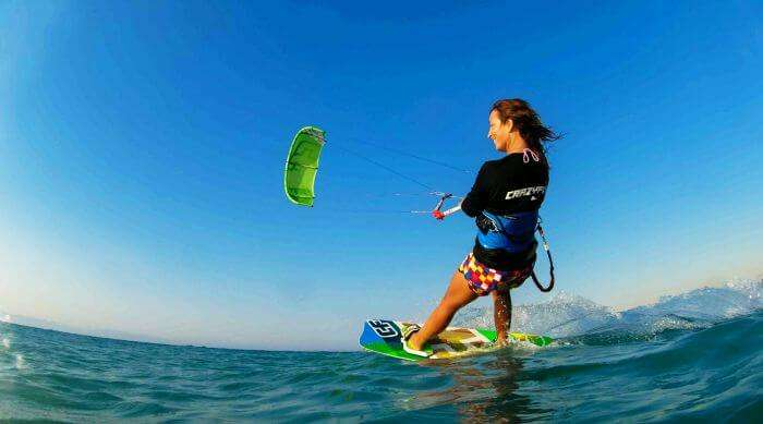 A free-spirited woman enjoys kiteboarding at Le Morne Beach Mauritius