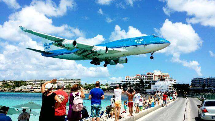 Tourists clicking a picture of the plain flying over Maho Beach