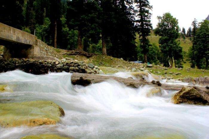 Water flows under a bridge in the valley of Kashmir