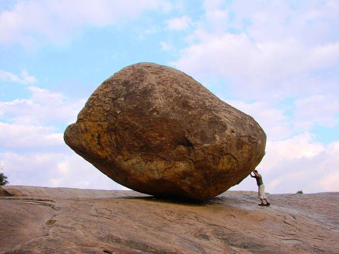 A man tries to push the intriguing balancing rock off balance at Jabalpur