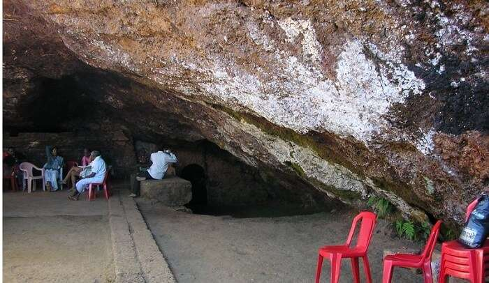 People sit on chair outside the Nellitheertha cave