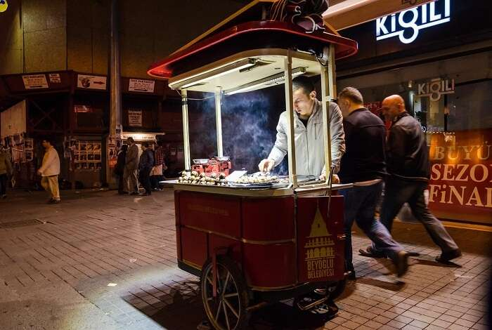 A common street food vendor cooks the local delicacies on a portable food cart