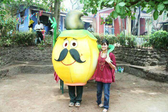 A tourist posing with the mascot of Cashew and Coconut festival in Goa