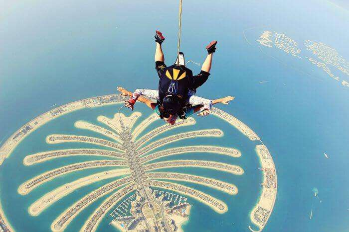 A couple hang-gliding above the world's only man-made island in the shape of a tree – Dubai Palm Islands