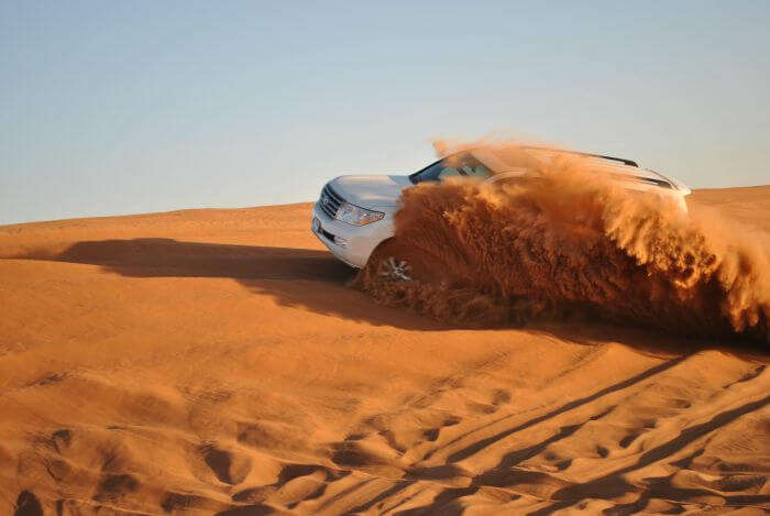 A SUV amidst red brown desert sand in Dubai