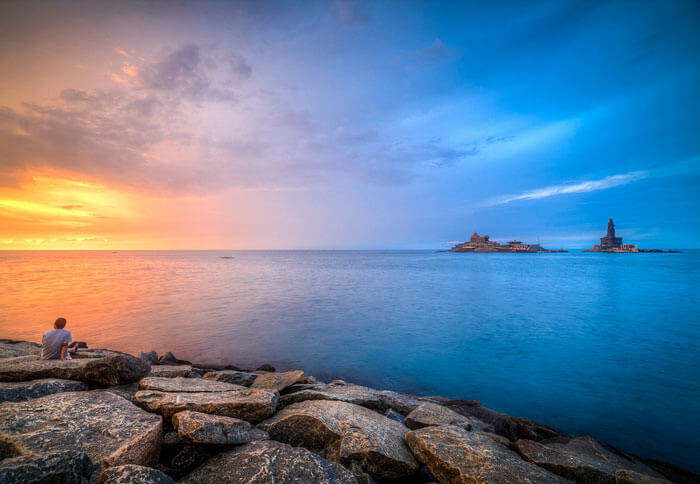 A lone traveler enjoys the magnificent sunrise at the Kanyakumari Beach