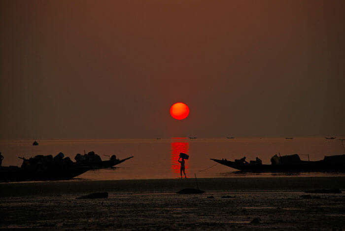Sun sets on Bay of Bengal at Frasergunj as fishermen return home from the sea
