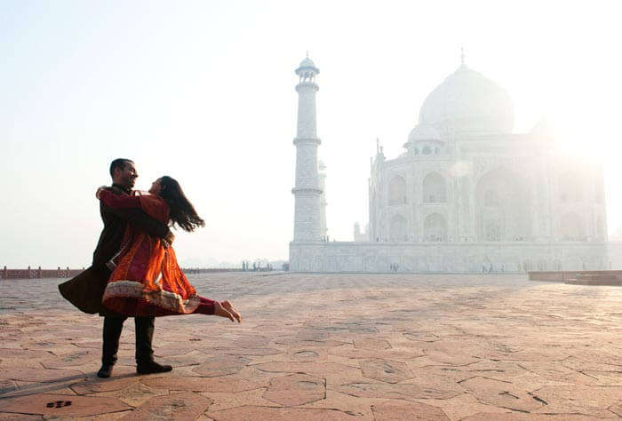 A couple enjoying a romantic moment with Taj Mahal in the backdrop