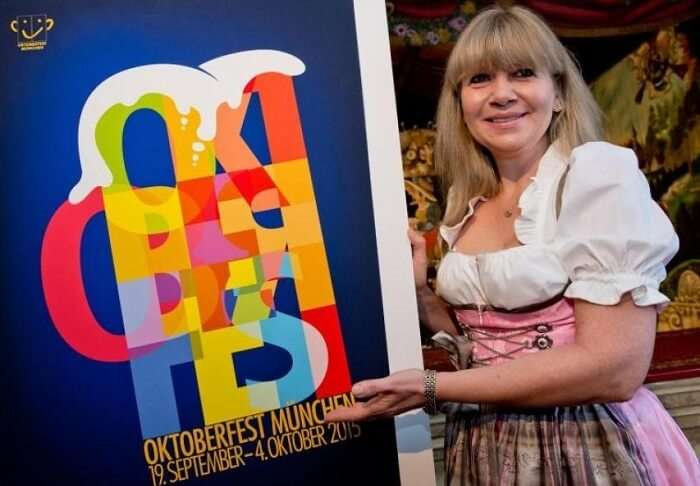 A lady poses with the promotional poster of the 2015 edition of Oktoberfest
