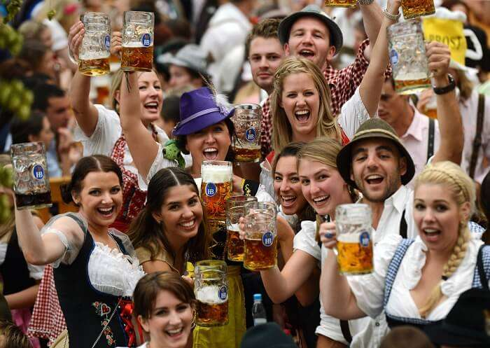 Visitors wearing traditional Bavarian clothes raise their beers in a festival tent at the start of the Oktoberfest beer