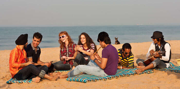 Friends relax and enjoy music at one the beaches at Goa