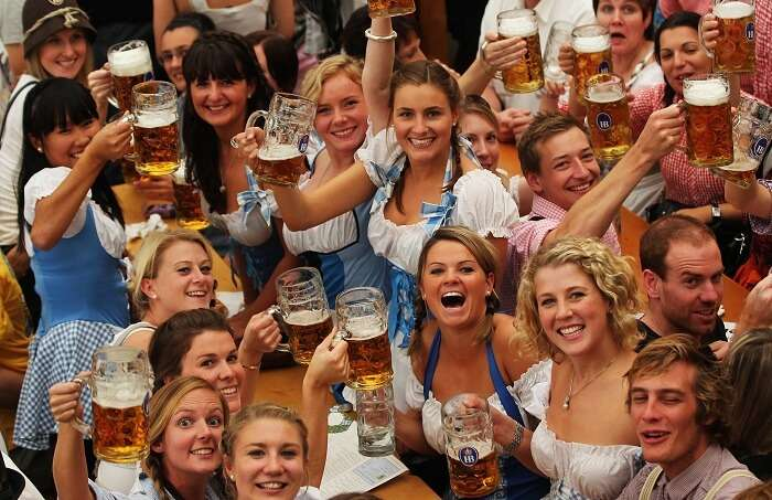 Several young maids dressed in traditional attire pose with beer at Oktoberfest