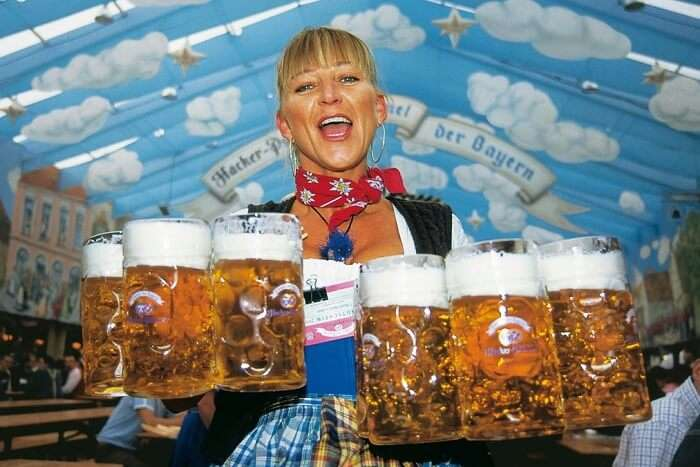 A beautiful waitress poses with beer liters in both hands
