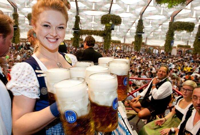 A beautiful waitress holds many liters of beer in a tent