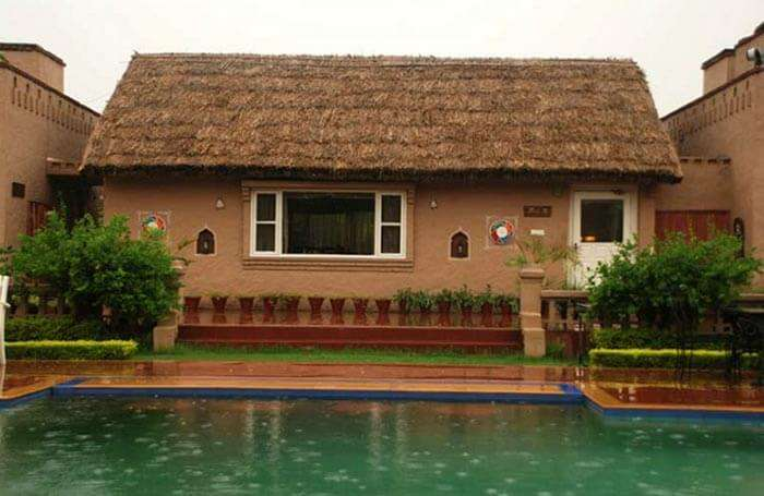 Exterior view of the Hut-K restaurant at Aura Vaseela resort near Chandigarh on a rainy day