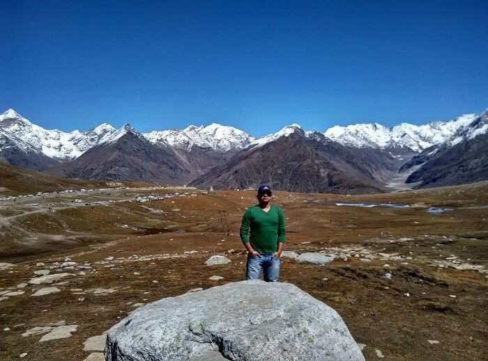 Rajeev in the background of hills in Rohtang Pass
