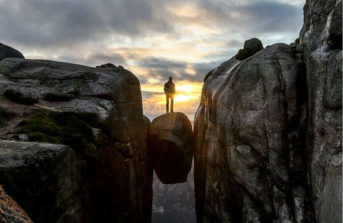 A man poses on the balancing rock 1000 meters above sea level at Kjragbolten in Norway