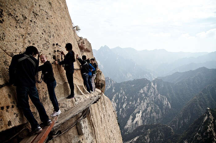 Tourists walk on a thin plank at Mount Hua in China
