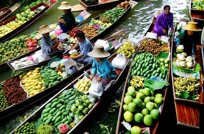 Vendors selling exotic fruits and vegetables on their boats in the famous Floating Market of Solomon Islands.
