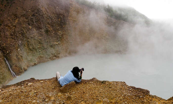 A young lady takes a snap at the boiling lake of Dominica