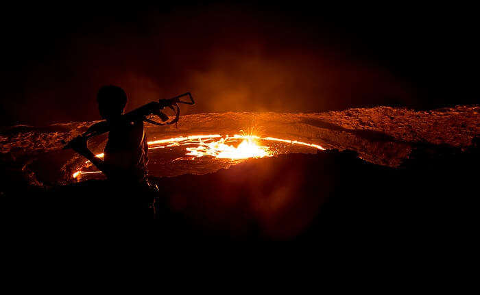 A man at night takes guard at the Erta Ale Volcano