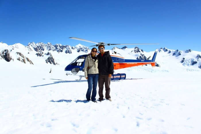 A couple poses with the helicopter used on the heli-hike at Fox Glacier