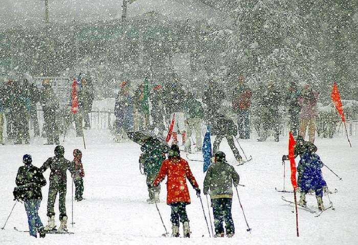 Tourists skiing under snowfall in Patnitop