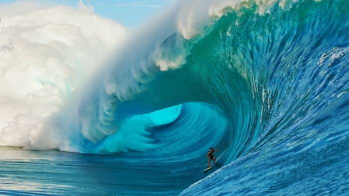 A man surfing on a gigantic wave