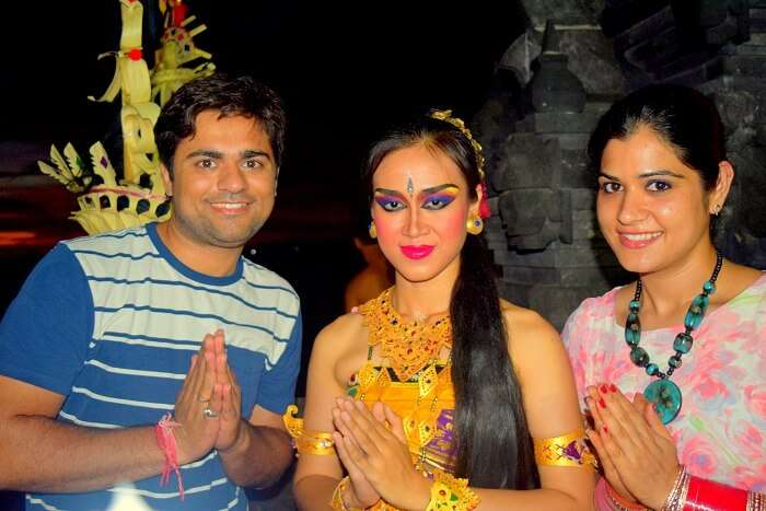 Antriksh and his wife pose with a Kechak dancer in Bali