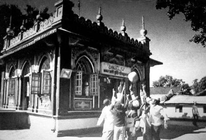 People lifting the levitating stone at Hazrat Qamar Ali Darvesh shrine, Shivapur