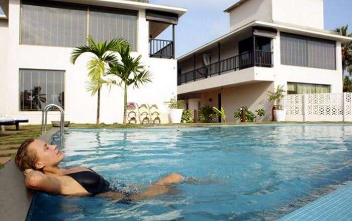 A girl lounging in the pool of the O Hotel in Goa near Calangute beach