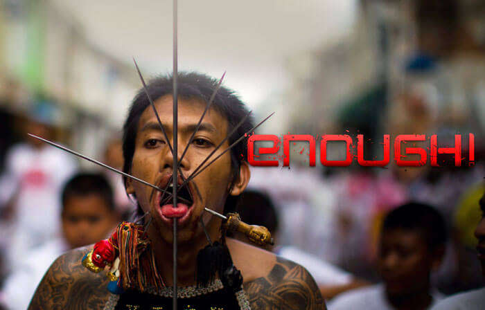 A participant with skewers pierced in his mouth during Vegetarian festival in Thailand